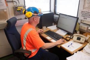 Kuvituskuva: työntekijä suojavaatteissaan tietokoneen äärellä tehtaan toimistossa.