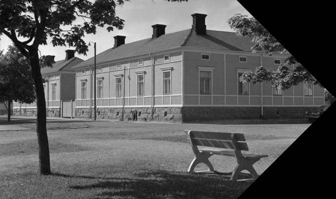 Mustavalkoinen kuva puurakennuksesta. Etualalla puistonpenkki.
