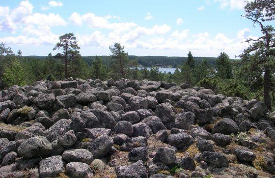 Kuvan etualalla on laidasta laitaan harmaita pyöreäkulmaisia kivenmurikoita, jotka muodostavat pronssikautisen röykkiöhaudan kummun. Kivien takana aukeaa kaunis havumetsäinen maisema, jonka keskellä näkyy sinistä merenlahtea.