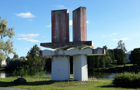 Kuvassa keskellä kaksipylväinen patsas, jonka takana näkyy joki ja puustoa.