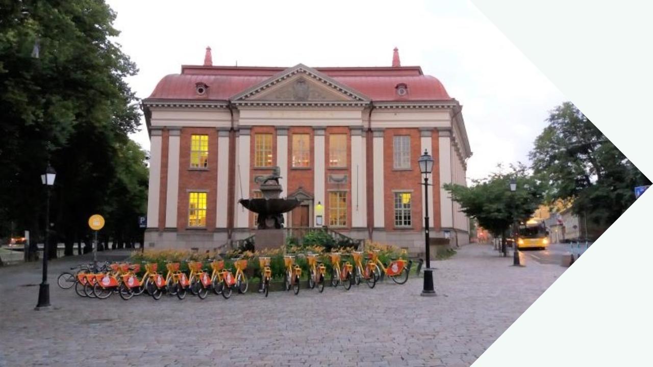 Kuvassa on keskellä Turun pääkirjaston vanha rakennus, joka edustaa myöhäisrenessanssia. Se on punatiilinen ja sen seinissä on lähes katutasosta katonrajaan asti ulottuvia valkoisia koristepylväitä. Talon edustalla on suihkulähde ja suihkulähteen edustalla keltaisten Föli-kaupunkipyörien puoliympyrän mallinen parkkipaikka. Rakennuksen vasemmalla puolella kulkee Läntinen Rantakatu ja Aurajoki ja oikealta puolelta alkaa Linnankatu, jossa seisoo keltainen bussi pysäkillään.