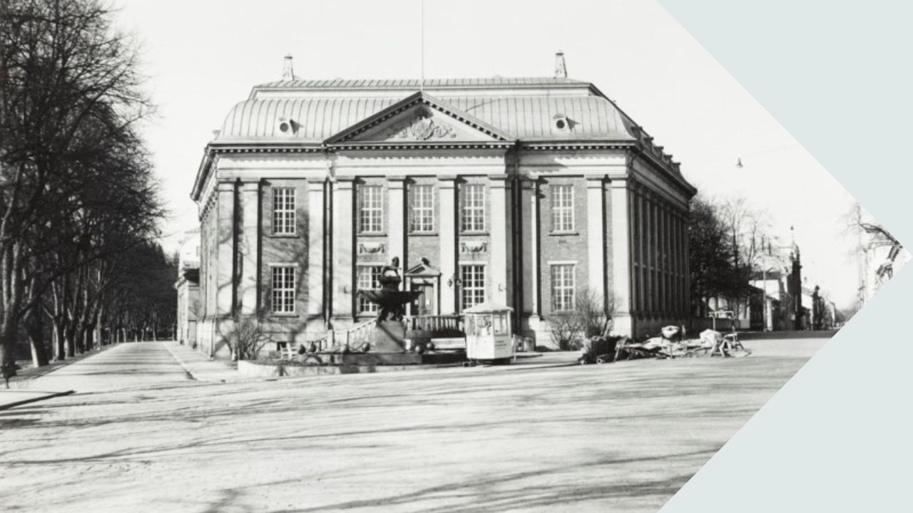 Mustavalkoisen kuvan keskellä on Turun pääkirjaston vanha rakennus, joka edustaa myöhäisrenessanssia. Se on punatiilinen ja sen seinissä on lähes katutasosta katonrajaan asti ulottuvia valkoisia koristepylväitä. Talon edustalla on suihkulähde, jonka oikealla puolella on pieni kuusikulmainen kioski. Rakennuksen vasemmalla puolella kulkee Läntinen Rantakatu ja Aurajoki ja oikealta puolelta alkaa Linnankatu.