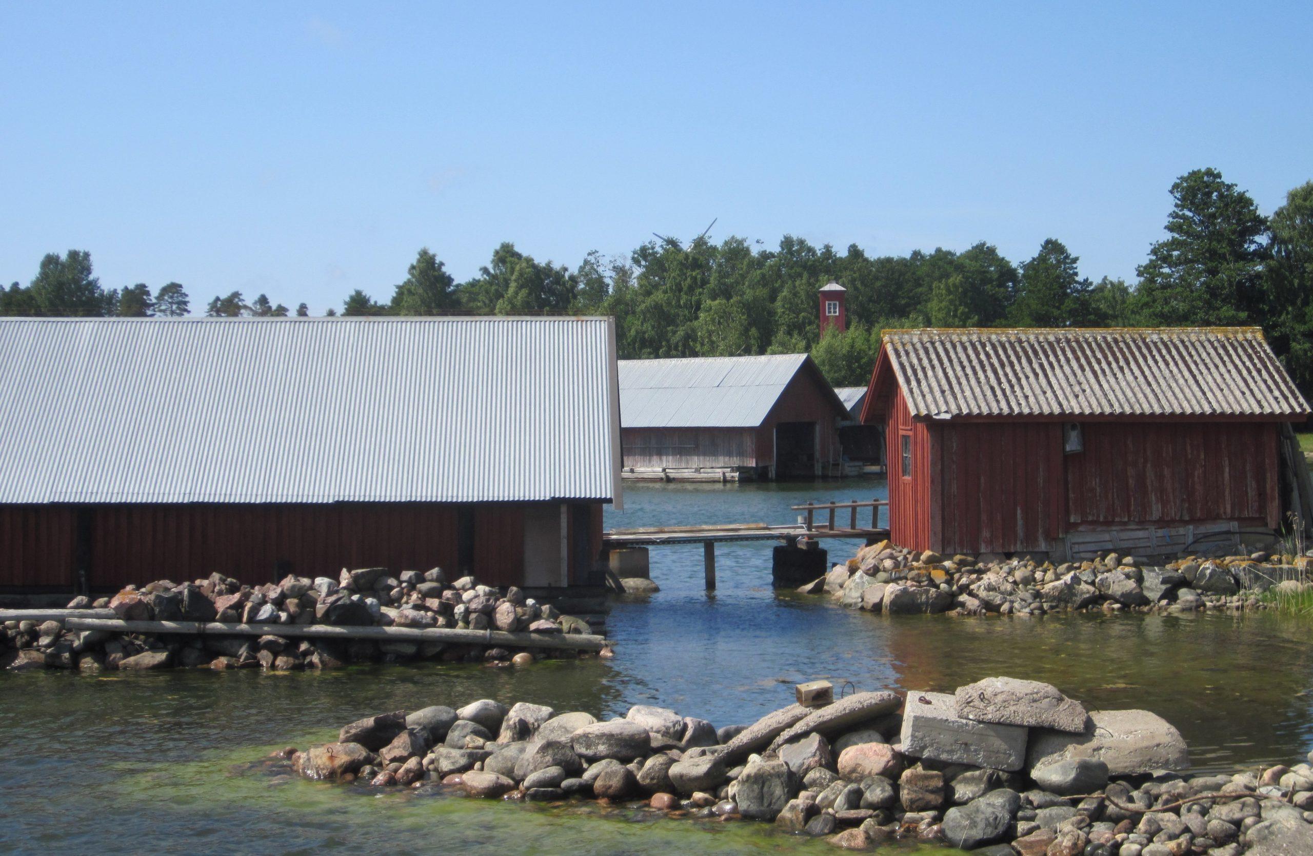 Mereltä päin otetussa rantakuvassa on isoista kivenmurikoista rakennettu aallonmurtaja sekä useita puisia yksikerroksisia venesuojia. Taustalla puita.