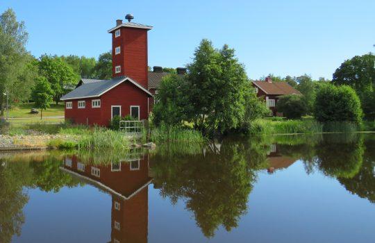 Kuvassa joen toisella puolella punainen puurakennus, jossa korkea torni. Vieressä puiden takana myös kaksi punaista taloa.