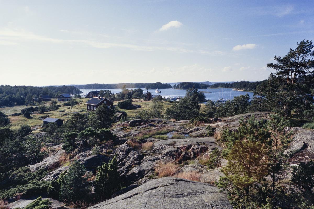 Kuvan etualalla on rosoista kalliota, jolla kasvaa ruohoa ja kituliaita havupuita. Kallion ja merenrannan väliin jää ruohoinen alue, jolla on puutaloja. Merellä näkyy myös sankkapuustoisia saaria.