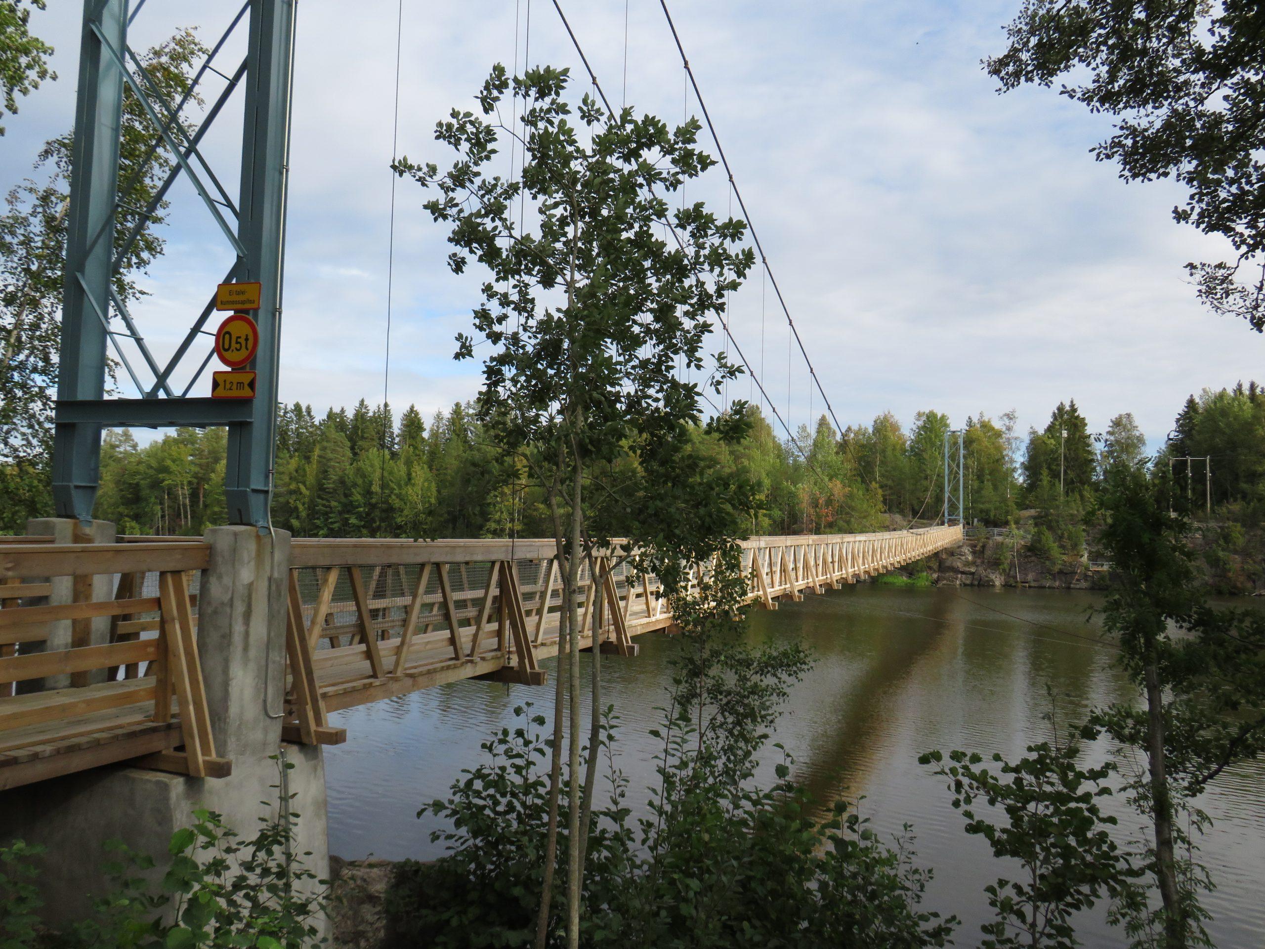Kuvassa pitkä puinen riippusilta, joka kulkee joen yli. Edessä puita ja taustalla vastarannalla kalliota ja metsää.