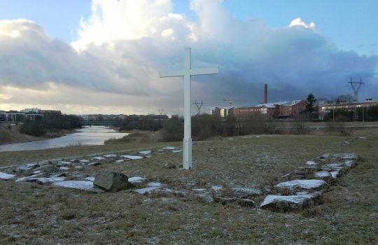 Kuvassa on maahan painunut neliön mallisen rakennuksen kivijalka, jonka keskellä on korkea valkoinen puuristi. Taka-alalla näkyy punatiilisiä tehdasrakennuksia. Vasemmalla virtaa Aurajoki ja sen vasemmalla puolella näkyy kerrostaloja.