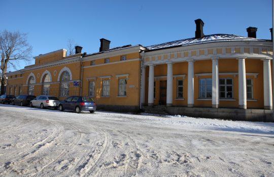 Talvikuvassa keltainen kivirakennus, jossa oikeassa reunassa kuusipylväinen rakennussiipi.