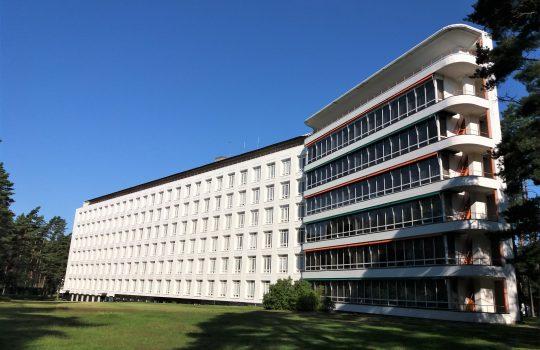 Kuvassa pitkä valkoinen kuusikerroksinen rakennus. Oikean laidan päädyn kulma on pyöristetty ja siinä on avoin porraskäytävä ylös asti. Oikean siiven ikkunat ovat aivan vieri vieressä niin, että koko seinä näyttää pelkältä lasilta. Rakennuksen vasemman siiven lukuisat ikkunat ovat yksitellen suorissa riveissä.