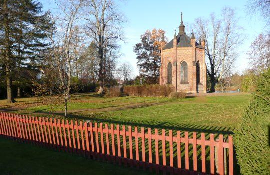 Kuvassa edessä punaista puuaitaa ja taustalla näkyy tiilinen uusgoottilainen kappeli.
