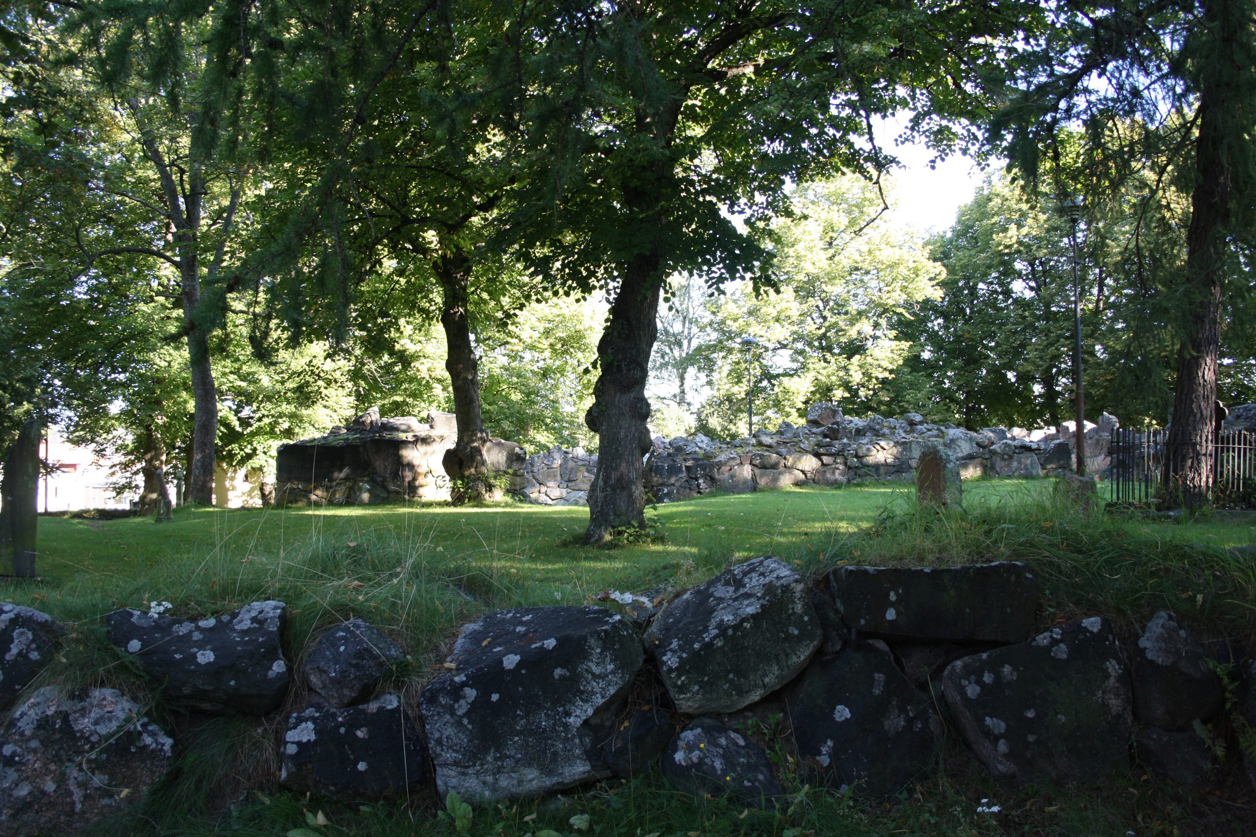 Kuvassa näkyy niin sanotusti kivinen aitaus, joka rajaa sisällensä vehreää nurmikkoa.