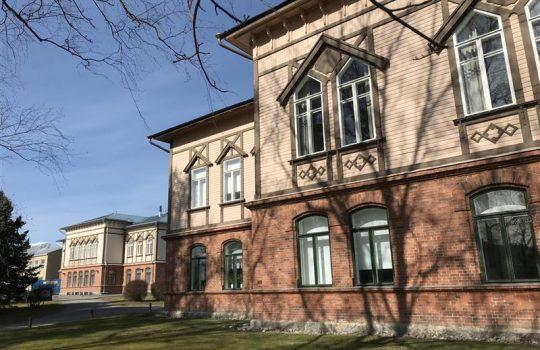 Kuvassa oikealla edustalla on rakennus, jossa alaosa tiiltä ja yläosa puuta. Vasemmalle mentäessä taustalla näkyy samantyylinen toinen rakennus.