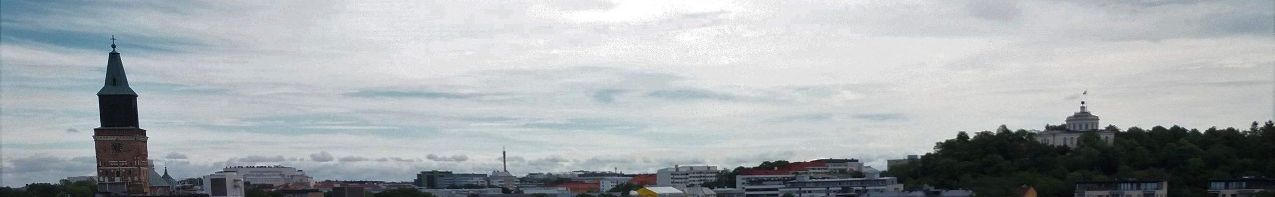 Siluettikuva Turun kaupungin kattojen yli. Vasemmassa laidassa näkyy tuomiokirkon torni ja oikealla Vartiovuoren laella tähtitorni. Näiden välissä näkyy monien eri aikakausien rakennusten kattoja.