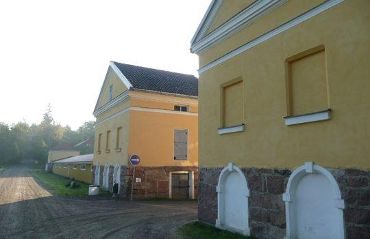 Kuvassa on kolme kuution mallista keltaista rapattua kivirakennusta. Kahden ensimmäisen välistä johtaa hiekkatie oikealle. Toisen ja kolmannen välissä on pitkä matala keltainen puinen varastorakennus. Taustalla näkyy vihreitä lehtipuita.