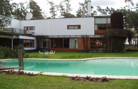 Kuvassa edessä pyöreäkulmainen uima-allas. Taustalla moderni valkoinen kivirakennus puisine ikkunakarmeineen.