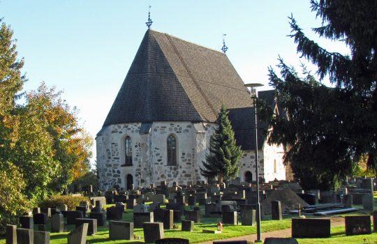 Kuvan etualalla on hautausmaa hautakivineen. Taustalla on valkoiseksi rapattu harmaakivikirkko, jonka musta katto nousee korkealle kohti taivasta.