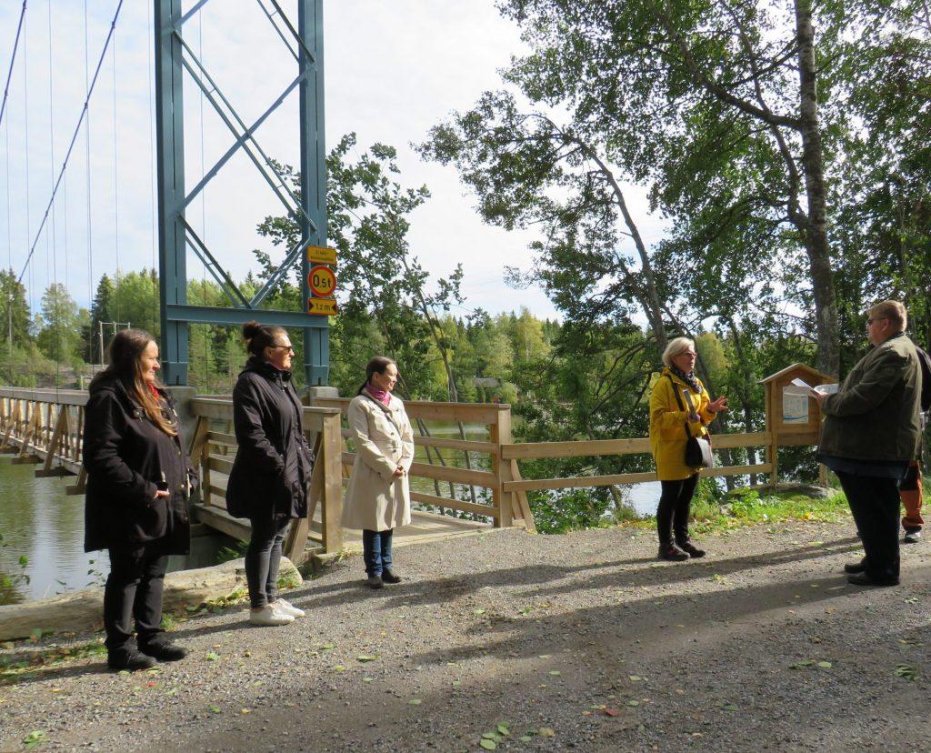 Kuvassa Satakunnan kulttuuriympäristötyöryhmän edustajat luovuttavat palkintoa riippusillan edessä.