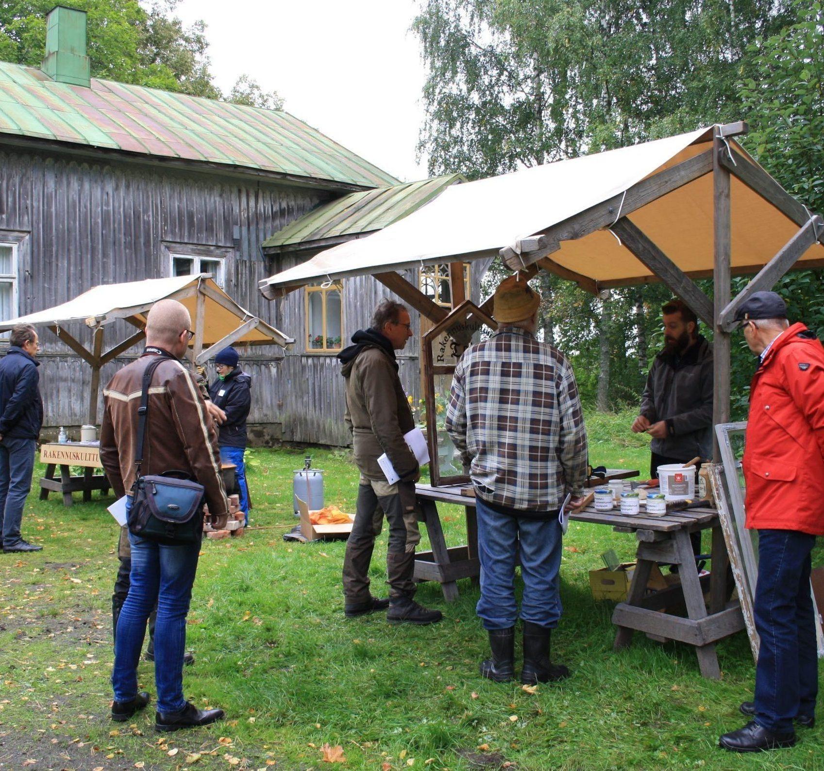 Kuvassa ihmisiä kokoontuneena harmaan puutalon pihaan neuvontakojujen ääreen.