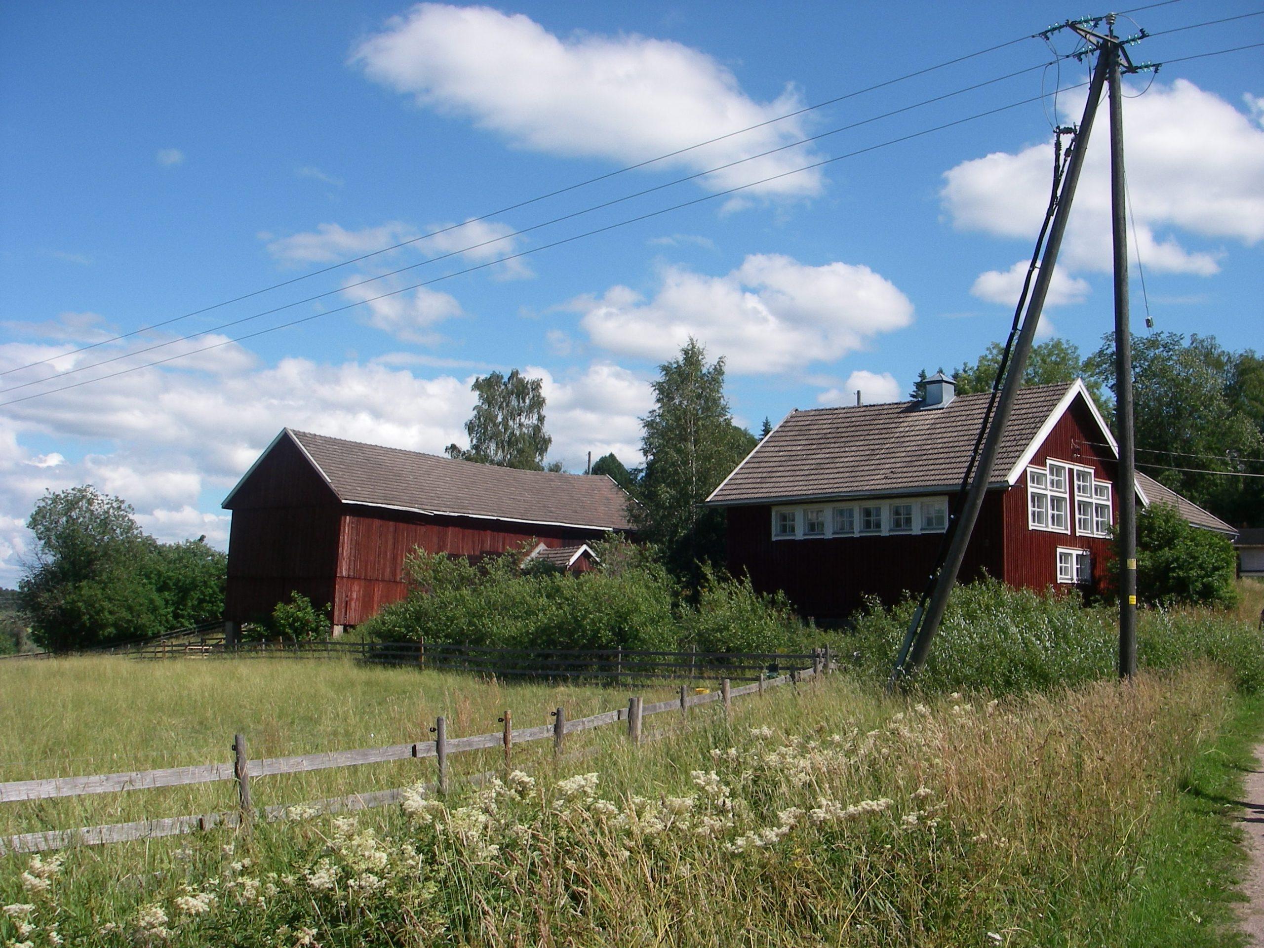 Kuvassa kaksi punaista puutaloa ja niiden edessä laidunta sekä sähkötolppa.