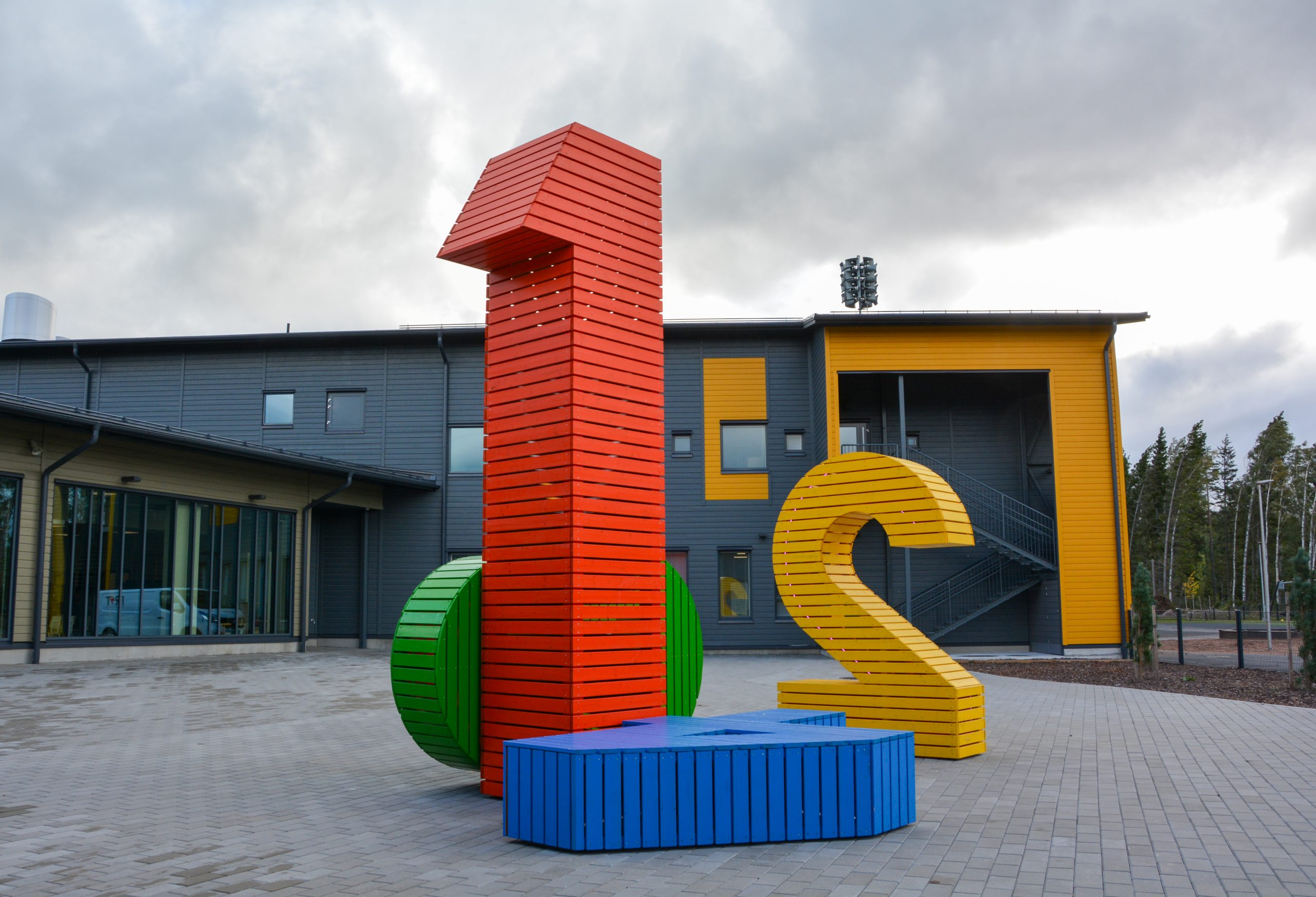 Kuvassa koulurakennuksen pihassa eri värisistä numeroista koostuva teos. Punainen numero yksi seisoo keskellä. Takana keltainen numero kaksi. Muutama numero kallellaan.